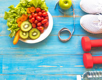 Healthy lifestyle for women diet with sport equipment, sneakers, measuring tape, vegetable fresh, green apples and bottle of water Stock Photo