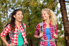 Healthy lifestyle women laughing hiking in forest. Healthy lifestyle women laughing hiking walking forest doing outdoor activity having fun together stock photo