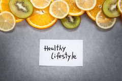 Healthy lifestyle words with fruits on gray background Royalty Free Stock Photo
