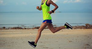 Young fitness woman running at morning beach. Healthy lifestyle young fitness woman running at morning beach Stock Image