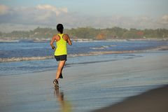 Young fitness woman running on sunrise beach. Healthy lifestyle young fitness woman running on sunrise beach Royalty Free Stock Photos