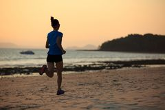 Fitness woman running at sunset beach. Healthy lifestyle young fitness woman running at sunset beach Stock Photo