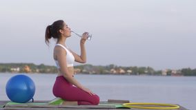 Healthy lifestyle, young smiling athletic female drinks mineral clear beverage from bottle while doing sports and enjoy. Rest in nature on river against sky stock video