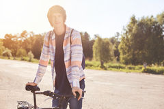 Healthy lifstyle. Portrait of active and sport teenager on bike ride standing on asphalt outdoor. Young male having calm holiday t Royalty Free Stock Photo