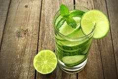 Healthy lime and cucumber water against wood. Healthy vitamin water with lime and cucumber in a glass against and rustic wood background royalty free stock photo