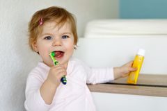 Little baby girl holding toothbrush and brushing first teeth. Toddler learning to clean milk tooth. stock image