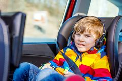 Healthy little blond kid boy watching tv or dvd with headphones during long car driving on family vacations. Leisure for. Children for long drive. Preschool royalty free stock image