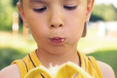 Healthy little boy eating bananaon nature background. Happy kid enjoy eating fresh fruit. Stock Photos