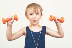 Healthy little boy working out with dumbbells over white background. Healthy lifestyle, kids sports and childhood. Cute kid boy ex stock photography