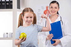Healthy little girl. Cheerful little girl holding apple and smiling while doctor standing on background Stock Photo
