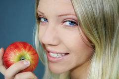 Healthy living. A smiling young blond woman is holding a apple in her hand Stock Photos