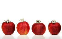 Healthy living. Red apple and cubes with letters in front of a white background - diet Royalty Free Stock Images