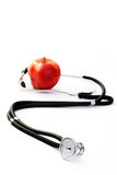 Healthy living. Stethoscope and red apple on white - healthy living Stock Images