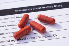 Healthy living questionnaire. Group of pills on a questionnaire form presenting statements about healthy lifestyle Stock Photography