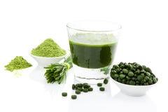 Healthy living. Spirulina, chlorella and wheatgrass. Green food supplement. Spirulina, chlorella and wheatgrass. Green juice, green pills, wheatgrass blades and Royalty Free Stock Photos