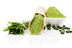 Healthy living. Spirulina; chlorella and wheatgrass. Green food supplement. Green pills; wheatgrass blades and ground powder on white background. Healthy Royalty Free Stock Photos