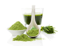 Healthy living. Wheatgrass. Green food supplement. Wheatgrass blades, green ground powder and green drink on white background. Healthy lifestyle Royalty Free Stock Photos
