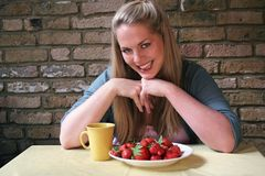 Healthy Living - woman and strawberrys. Image of a blond woman about to eat a plate of fresh strawberries, conceptual healthy lifestyle choices royalty free stock photography