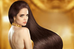 Healthy long Hair. Brunette girl. Beauty Model portrait. Beautif. Ul woman with long smooth shiny straight wavy hair. Fashion golden earring jewelry. Hairstyle Royalty Free Stock Images