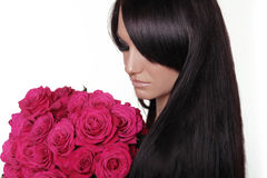 Healthy long hair. Brunette woman with fringe holding pink bouqu Stock Image