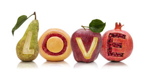 Healthy Love. Isolated Pear, Grapefruit, Apple and Pomegranate on white background wiht cut out letters forming the word LOVE Stock Photos