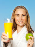 Healthy lovely young woman dieting. Beautiful girl holding orange juice and green fresh apple fruit, happy smiling female portrait outdoor over blue sky Royalty Free Stock Photo