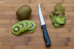 Healthy low calories ingredients: Kiwi peeled in cutting board. Kiwifruit on a wooden chopping board with a knife.  There is one uncut kiwifruit and some round Stock Images