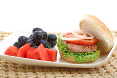 Healthy low fat chicken burger with fruit isolated. On white Royalty Free Stock Photography