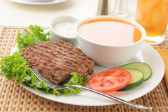 Healthy low fat meal. A healthy diet meal with a broiled hamburger patty, tomato, cucumber and soup royalty free stock image