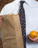 Healthy Lunch. Closeup businessman showing off his healthy lunch featuring a paper bag and a fresh orange Royalty Free Stock Photography