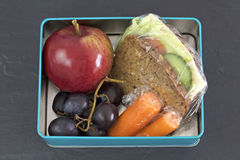 Healthy lunch box, cheese sandwich, apple, carrots and grapes. Stock Photo