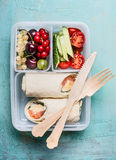 Healthy lunch box with salmon tortilla wraps and wooden cutlery , fruits and vegetables Royalty Free Stock Photo