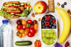 Healthy lunch box with sandwich and fresh vegetables, bottle of. Water and fruits on wooden background. Top view Royalty Free Stock Photography