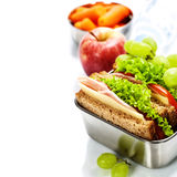 Healthy lunch. Lunch box with sandwich, fruits and water on white background stock photo