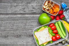 Healthy lunch boxes with sandwich, eggs and fresh vegetables, bottle of water, nuts and fruits. On rustic wooden background. top view with copy space Stock Images