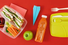 Healthy lunch boxes sandwich vegetables juice top view Flat lay. Healthy lunch boxes with sandwich and fresh vegetables, bottle of juice and paper plane on red Royalty Free Stock Photo