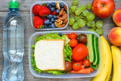 Healthy lunch boxes with sandwich and fresh vegetables, bottle of water, nuts and fruits. On rustic wooden background. top view Royalty Free Stock Image