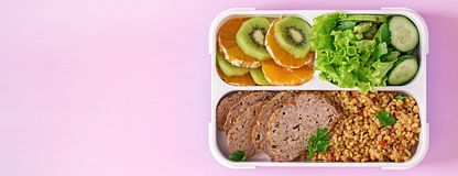 Healthy lunch with bulgur, meat and fresh vegetables and fruit. On a pink background. Fitness and healthy lifestyle concept. Lunchbox. Top view stock photo