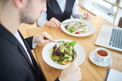 Healthy lunch. Fresh vegetable salad on plates of two employees networking during lunch in cafe Stock Images