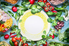 Healthy lunch preparation. Various vegetables and salad bowls in plastic packaging around empty plate. Top view, frame Stock Photos