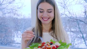 Healthy lunch, smiling female eats useful food in background of window inside. Healthy lunch, smiling female eats useful food in background of large window stock footage