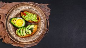 Healthy lunch snack, three delicious avocado sandwiches, fresh sliced avocados, on an earthenware plate, copy space on a black sto. Ne background, copy space Stock Photo