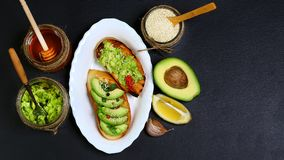 Healthy lunch snack, three delicious avocado sandwiches, fresh sliced avocados, honey, sesame seeds on an earthenware plate, copy. Space on a black stone Royalty Free Stock Images