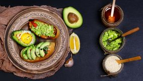 Healthy lunch snack, three delicious avocado sandwiches, fresh sliced avocados, honey, sesame seeds on an earthenware plate, copy. Space on a black stone Stock Image