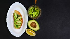 Healthy lunch snack, three delicious avocado sandwiches, fresh sliced avocados, on an plate, copy space on a black stone backgroun. D, copy space, top view, set Royalty Free Stock Images