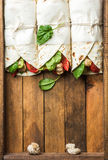 Healthy lunch snack. Three tortilla wraps with grilled chicken fillet and fresh vegetables on rustic wooden tray Royalty Free Stock Photo