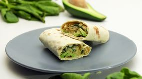 Healthy lunch snack. Tortilla wraps with Avocado, Spinach, Cheese and Bell Pepper on a Grey Plate. On a White Background stock images