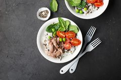 Healthy lunch. Tuna, wild rice and basmati, tomatoes, spinach and green peas in serving bowls. Top View. Stock Photos