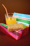 Healthy lunchbox. Containing orange juice, apple and an oat bar Stock Images