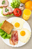 Healthy lunchtime with two eggs,bacon with toast with juice on a plate. On linen background Royalty Free Stock Photography
